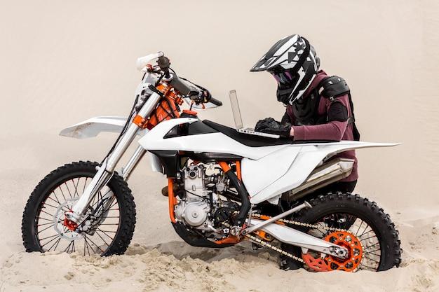 オートバイのライダーが砂漠でラップトップを閲覧