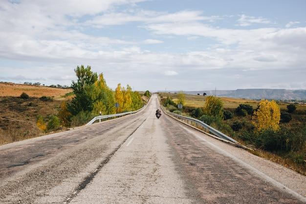 Motociclista sulla strada di campagna vuota