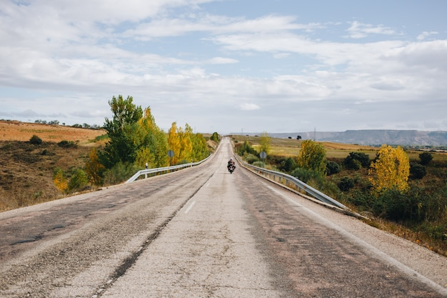 Мотоциклист на пустой проселочной дороге