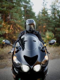 Мотоциклист в шлеме смотрит прямо перед собой с включенными фарами. понятие автоспорта, скорости и свободы