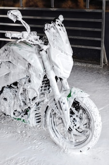 A motorcycle in soap at the car wash washes