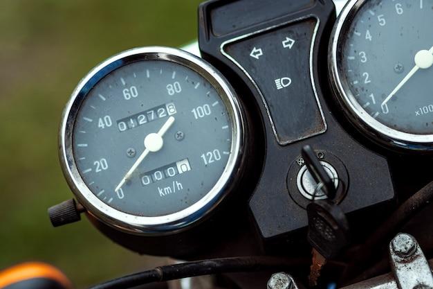 オートバイのスピードメーターのクローズアップ、バイクに乗って道路に。