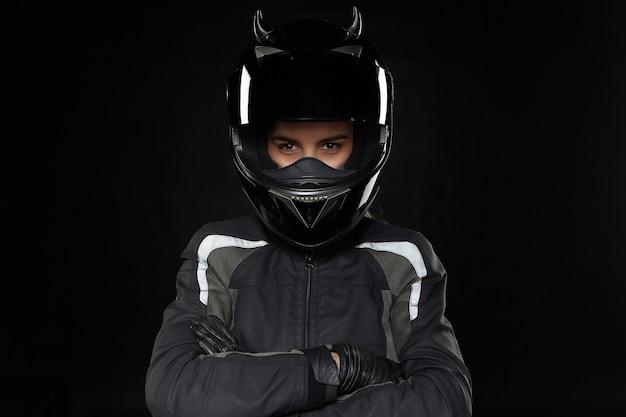 Мотоциклетный спорт, экстрим, соревнования и адреналин. активная молодая гонщица в защитном шлеме и форме собирается участвовать в шоссейных гонках или мотокроссе, скрестив руки на груди