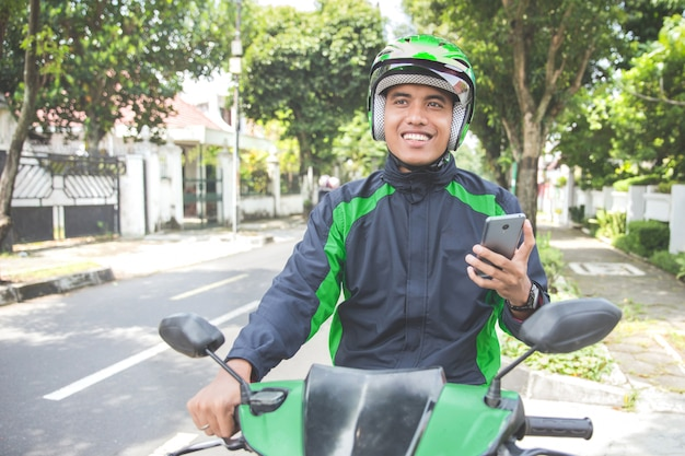 Motorcycle taxi driver taking order via mobile phone online app