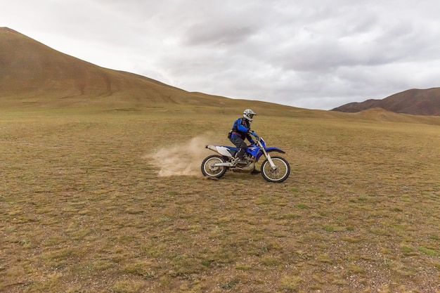 Motorcycle traveler man in helmet riding a motorbike in the steppes of mongolia.