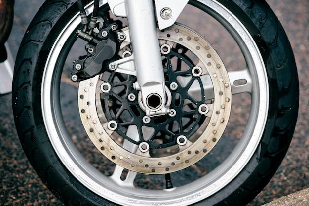 ディスクブレーキシステムと金属スポークを備えたオートバイホイール。バイクのフォークとタイヤの詳細な写真をクローズアップ。交通手段。最新の運転技術