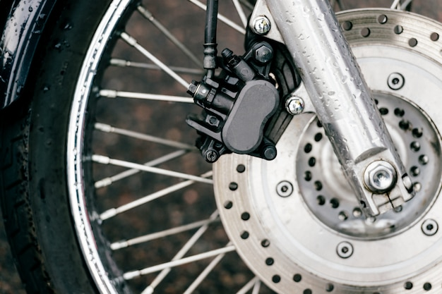 Motorcycle wheel with disk brakes system and metal spokes. closeup detailed photo of motorbike forks and tire. different parts of two-wheeled vehicle.  transportation. modern driving technologies
