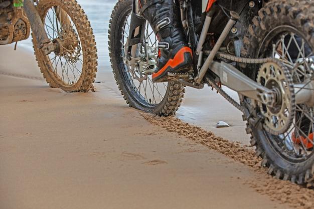 オートバイの車輪は浜辺の濡れた砂に足跡を残す