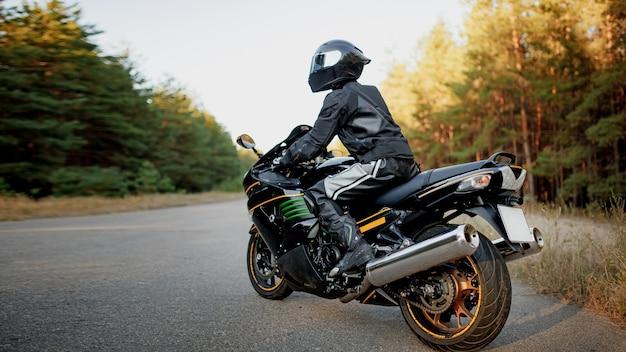 ヘルメットと革の保護具を身に着けた道路上のモーターサイクリストだけが、森の背景にある高速スポーツバイクに座って横を向いています