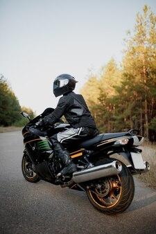 Мотоциклист в шлеме на мотоцикле на проселочной дороге.
