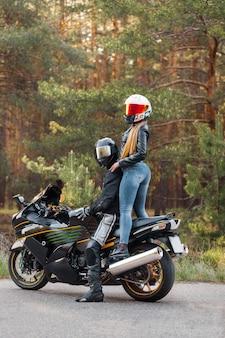 革のジャケットを着たモーターサイクリストがバイクに座り、森の木々を背景にヘルメットをかぶったバイクに女の子が立っている