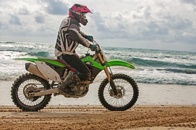 保護服を着たモーターサイクリストは、海の上のオートバイの車輪に乗り、水しぶきが車輪の下から飛びます。