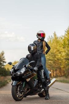 革のジャケットとヘルメットのモーターサイクリストは、スポーツバイク、女の子のスタンド、ぼやけた背景、コピースペースに座っています