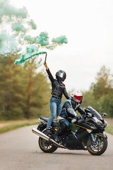 革のジャケットとヘルメットのモーターサイクリストは、スポーツバイク、女の子のスタンド、煙でぼやけた背景、コピースペースに座っています