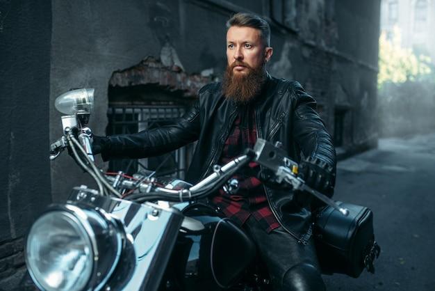 Мотоциклист в кожаной куртке позирует на чоппере