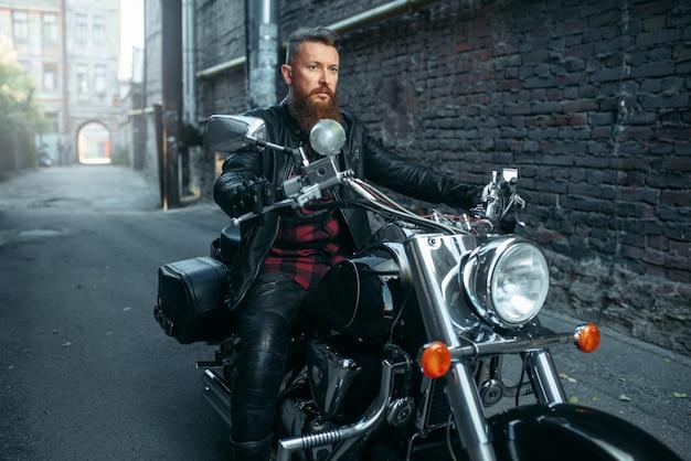Мотоциклист в кожаной куртке позирует на классическом чоппере. винтажный велосипедист на мотоцикле, образ жизни свободы