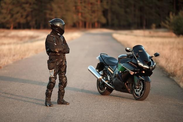 Мотоциклист в кожаном костюме и шлеме стоит на дороге и смотрит на спортивный мотоцикл
