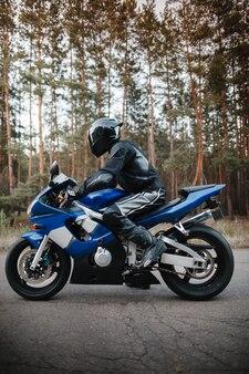 Мотоциклист в кожаном защитном костюме и черном шлеме сидит на спортивном мотоцикле. байкер в черном едет по дороге против леса. вид сбоку