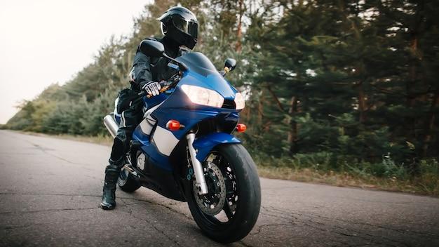 Мотоциклист в кожаном защитном костюме и черном шлеме сидит на спортивном мотоцикле. байкер в черном едет по дороге против леса