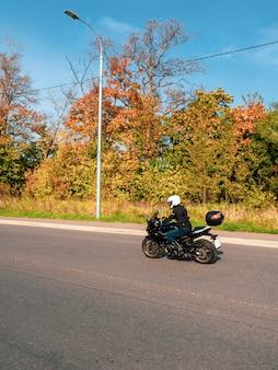 動いているモーターサイクリスト。田舎の秋の道を走る黒いバイクに乗ったバイカー。