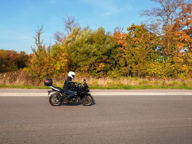 動いているモーターサイクリスト。田舎の秋の道の交通で黒いバイクに乗った女性バイカー。