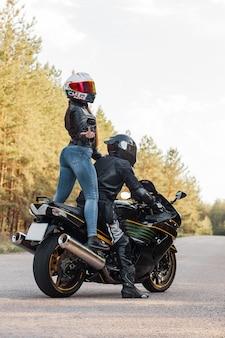 保護具とヘルメットのモーターサイクリストは、オートバイの女の子と一緒に座っている間、中指で性交を示しています
