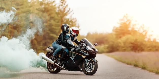 煙、コピースペースでぼやけた背景にスポーツバイクの女の子と一緒に座っている保護具とヘルメットのモーターサイクリスト