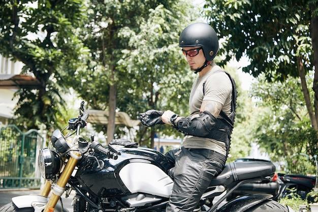Мотоциклист в снаряжении для верховой езды, шлеме и очках надевает кожаные перчатки, сидя на велосипеде