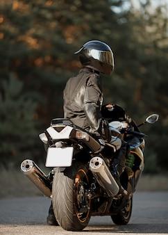 Мотоциклист на своем мотоцикле по дороге. человек на современном спортивном мотоцикле. концепция свободы и приключений. крупным планом вид сзади