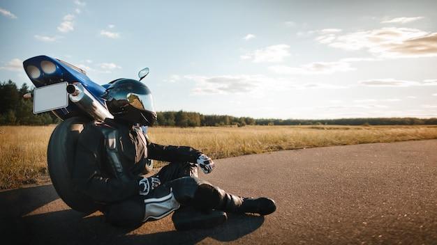Мотоциклист или байкер в черной кожаной куртке и защитном шлеме сидит возле спортивного мотоцикла на дороге и смотрит на закатное небо