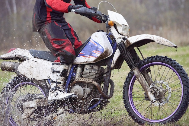 Motorcyclist racing in dirt while moving in front of camera