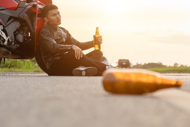 Motorcyclist sitting on the road beside his motorcycle and drinking beer