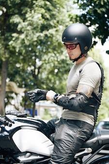 Мотоциклист надевает кожаные перчатки, шлем и защитные накладки для защиты