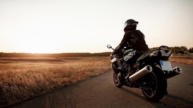 Мотоциклист в шлеме и снаряжении повернулся спиной на фоне красивого закатного света с копией пространства