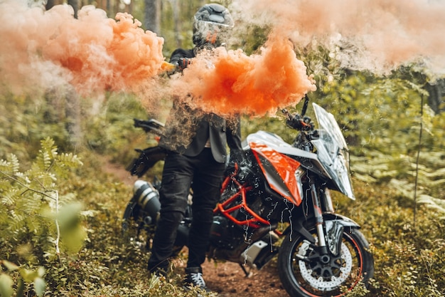 Motorcyclist with colorful smoke going from his hand in forest