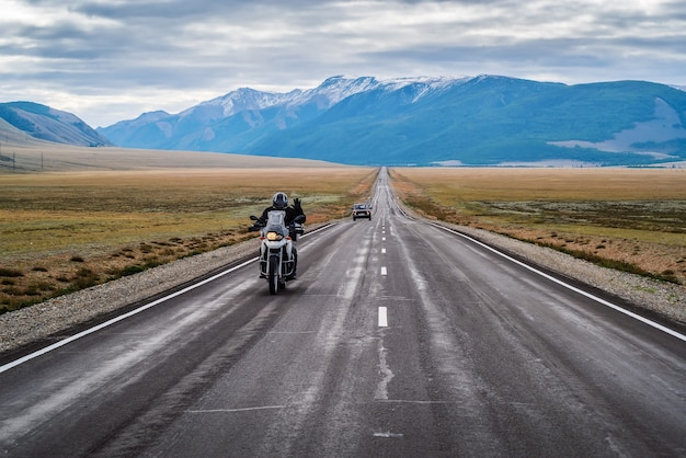 A motorcyclist with his hand raised in greeting, riding along the chuysky highway at dawn, landscape with a highway. russia, mountain altai