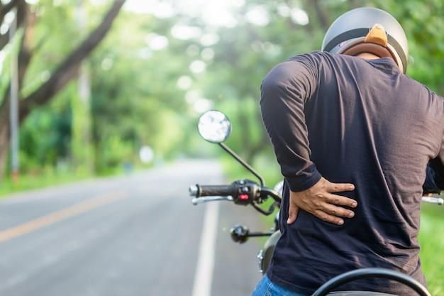 고통 또는 피곤 개념 모터 사이클 : 남자 라이더는 그의 뒷면을 만지고 긴 오토바이를 타고 피곤한 느낌. 복사 공간이있는 도로에서 야외 촬영