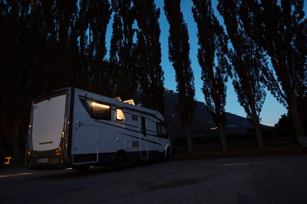 Motorhome camper vehicle for transport and vacation leisure people parked by night near a forest woods enjoying outdoors in travel lifestyle