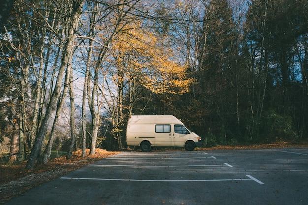 森の中の駐車場にキャンピングカーが駐車。キャンプと冒険の概念
