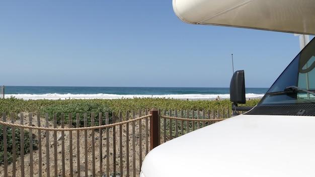 Автодом прицеп, караван для путешествия. набережная энсинитас, волны пляжа моря тихого океана, побережье калифорнии сша. отпуск на берегу моря, дом на колесах на колесах. дом на колесах на колесах. голубое небо.