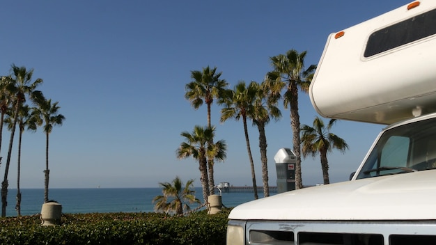 Автодом прицеп или караван для поездки. набережная тропических пальм и пляж тихого океана, калифорния, сша. отдых на берегу моря в автофургоне, доме на колесах на колесах. дом на колесах на колесах.