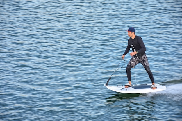 Участник мотосерфинга на скорости выезжает на поворот, образуя много брызг. реактивный серфинг на воде, человек катается на доске для струйного серфинга. серфер в движении, летний спорт