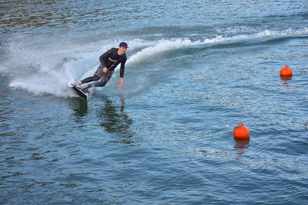 モトサーフのライバルがスピードを出して大量のスプレーをしている。水上でのジェットサーフィン、ジェットサーフボードに乗っている男。動きのあるサーファー、サマースポーツ