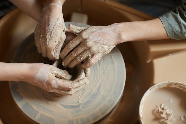 陶器のホイールで一緒に粘土を成形