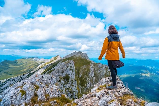 Гора айзкорри 1523 метра, самая высокая в гипускоа. страна басков. подъем через сан-адриан и возвращение через поля олца. молодая женщина в желтом, глядя на вид сверху