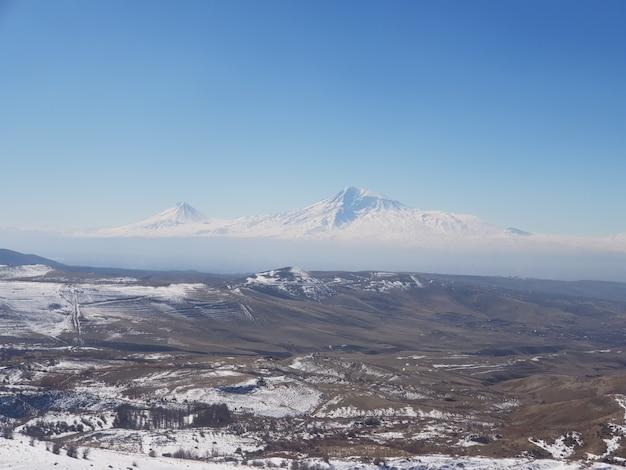 アルメニアの昼間の日光の下で雪に覆われたフィールドに囲まれたアララット山