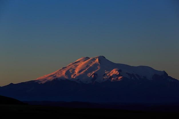夜明けにエルブルス山。北西からの火山の太陽に照らされた斜面の眺め。ロシアの北コーカサス。