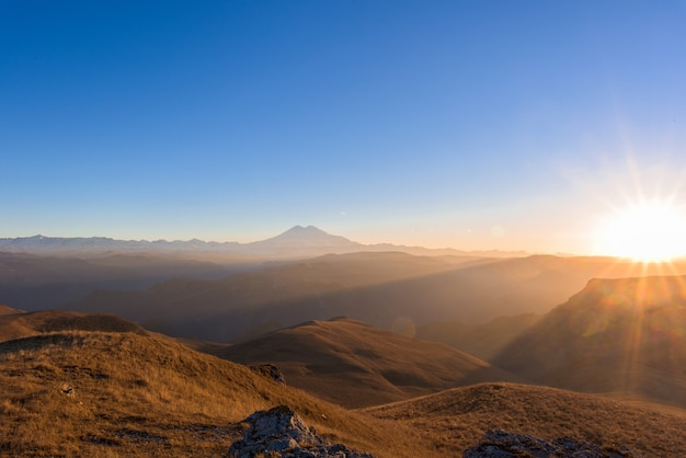 Mount elbrus on the horizon at sunset, illuminated by the sun. panorama of the mountain landscape.