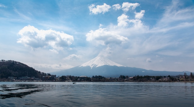 Mount fuji fujisan in midday from the boat at kawaguchigo lake with cloudy in the sky