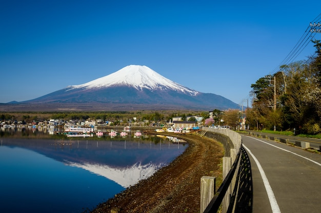 Mount fuji or fujisan at yamanaka lake shore street with city, and skyline reflection on water against blue sky in spring, yamanashi, japan. here is 1 of 5 mt. fuji lakes.
